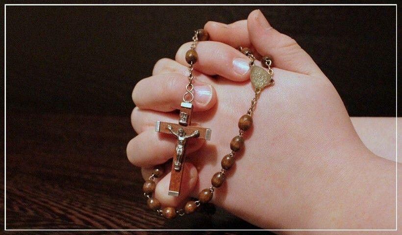 Manos con Rosario orando