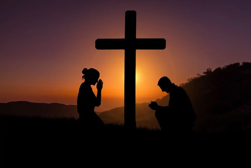 Siluetas personas orando junto ala cruz